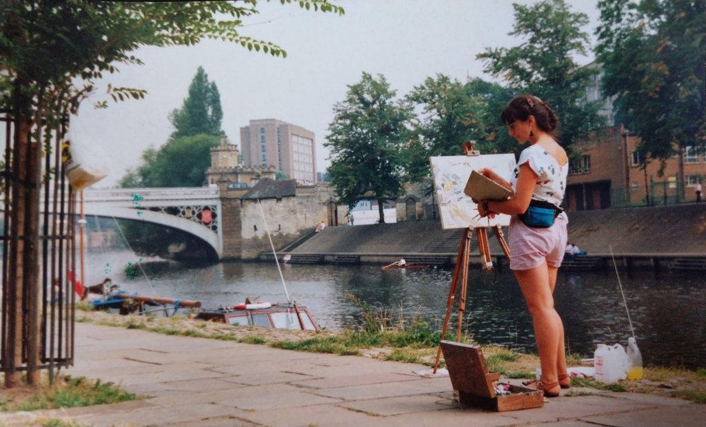 The artists Elaine Ask painting in York by the river Ouse in the 1980s